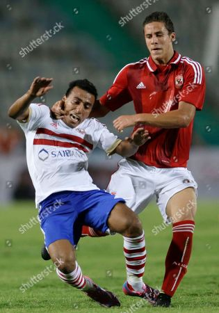Zamalek's Mohamed Abdel-Shafy, left, is fouled by Al Ahly's Saad Samir during their Egyptian Super Cup soccer match at the Cairo International Stadium in Cairo, Egypt, . The Egyptian football association (EFA) said that fans of Al Ahly and Zamalek clubs will not be allowed to attend the match. Egyptian authorities are limiting the number of soccer fans after the past three years of riots in stadiums
