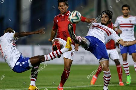 Al Ahly's Amr Gamal, center, is challenged for the ball by Zamalek's Mohamed Koffi, left, and Ali Gabr during their Egyptian Super Cup soccer match at the Cairo International Stadium in Cairo, Egypt, . The Egyptian football association (EFA) said that fans of Al Ahly and Zamalek clubs will not be allowed to attend the match. Egyptian authorities are limiting the number of soccer fans after the past three years of riots in stadiums