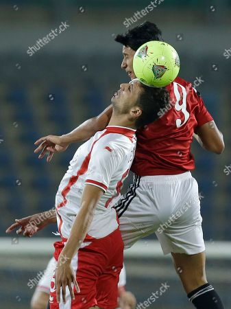 Egypt's Amr Gamal, right, and Tunisia's Rami Bedoui jump for the ball during their Africa Cup of Nations group G qualifying soccer match in Cairo, Egypt