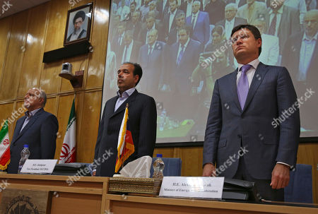 Bijan Namdar Zanganeh, Alexander Novak, Mohsen Jalalpour Russian Energy Minister Alexander Novak, right, Vice-President of Iran Chamber of Commerce, Industries, Mines and Agriculture Mohsen Jalalpour, center, and Iranian Oil Minister Bijan Zanganeh stand as they listen to their national anthems ahead of a joint meeting in Tehran, Iran, . Russian officials have traveled to Iran's capital to boost economic ties between the two countries. Zanganeh and Novak oversaw a meeting Tuesday of businessmen in Tehran, calling on them to increase trade