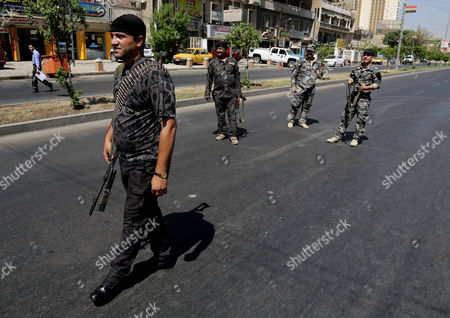 Iraqi army soldiers stand guard amid tight security measures in Baghdad, Iraq, Iraqi troops imposed heightened security in Baghdad Wednesday as international support mounted for a new prime minister to replace Nouri al-Maliki, who has called on the armed forces to stay out of politics amid fears of a possible coup