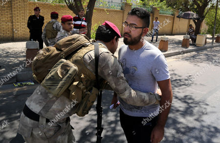 An Iraqi army soldier searches a man amid tight security measures in Baghdad, Iraq, Iraqi troops imposed heightened security in Baghdad Wednesday as international support mounted for a new prime minister to replace Nouri al-Maliki, who has called on the armed forces to stay out of politics amid fears of a possible coup