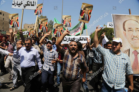 Pro-government supporters of Prime Minister Nouri al-Maliki, chant slogans during a demonstration in Baghdad, Iraq, . Tanks and Humvees were positioned on Baghdad bridges and at major intersections on Wednesday, with security personnel more visible than usual as pro-Maliki demonstrators took to Firdous Square in the capital, pledging their allegiance to him