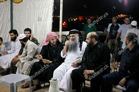 Abu Qatada, Abu Mohammed al-Maqdisi Radical al-Qaida-linked preacher Abu Qatada, center right, sits with the renowned jihadi ideologue, Abu Mohammed al-Maqdisi, center left, on the day Abu Qatada was released from Jordanian prison after an acquittal on security charges, in Amman, Jordan. Abu Qatada and Abu Mohammed al-Maqdisi, held court on the rooftop of a villa whispering to each other and rising occasionally from plastic chairs to greet supporters. The two have denounced some of the Islamic State group's practices as un-Islamic - comments some analysts say have turned the preachers into assets in Jordan's campaign to contain the Islamic State, which is believed to have attracted thousands of followers in Jordan