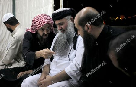 Radical al-Qaida-linked preacher Abu Qatada, center, listens to the renowned jihadi ideologue, Abu Mohammed al-Maqdisi, second left, on the day Abu Qatada was released from Jordanian prison after an acquittal on security charges, in Amman, Jordan. Abu Qatada and al-Maqdisi, held court on the rooftop of a villa whispering to each other and rising occasionally from plastic chairs to greet supporters. The two have denounced some of the Islamic State group's practices as un-Islamic - comments some analysts say have turned the preachers into assets in Jordan's campaign to contain the Islamic State, which is believed to have attracted thousands of followers in Jordan