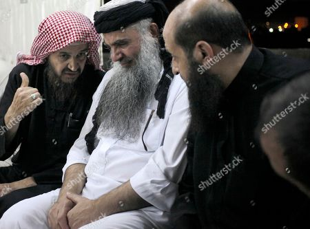 Abu Qatada, Abu Mohammed al-Maqdisi Radical al-Qaida-linked preacher Abu Qatada, second right, listens to the renowned jihadi ideologue, Abu Mohammed al-Maqdisi, left, on the day Abu Qatada was released from Jordanian prison after an acquittal on security charges, in Amman, Jordan. Abu Qatada and al-Maqdisi, held court on the rooftop of a villa whispering to each other and rising occasionally from plastic chairs to greet supporters. The two have denounced some of the Islamic State group's practices as un-Islamic - comments some analysts say have turned the preachers into assets in Jordan's campaign to contain the Islamic State, which is believed to have attracted thousands of followers in Jordan