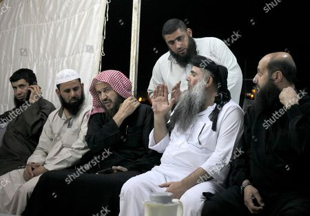 Abu Qatada, Abu Mohammed al-Maqdisi Radical al-Qaida-linked preacher Abu Qatada, second right, sits with the renowned jihadi ideologue, Abu Mohammed al-Maqdisi, third left, on the day Abu Qatada was released from Jordanian prison after an acquittal on security charges, in Amman, Jordan. Abu Qatada and al-Maqdisi, held court on the rooftop of a villa whispering to each other and rising occasionally from plastic chairs to greet supporters. The two have denounced some of the Islamic State group's practices as un-Islamic - comments some analysts say have turned the preachers into assets in Jordan's campaign to contain the Islamic State, which is believed to have attracted thousands of followers in Jordan
