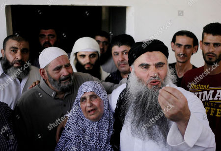 "Aisha, mother of radical al-Qaida-linked preacher Abu Qatada, center, holds him as he speaks after his arrival to his parents home in Amman, Jordan, . A Jordanian court on Wednesday acquitted Qatada - known for his fiery pro-al-Qaida speeches - of involvement in a plot to target Israeli and American tourists and Western diplomats in Jordan more than a decade ago. The three-judge panel unanimously acquitted Qatada ""because of the lack of convincing charges against him,"" said Judge Ahmed Qattarneh. His father Mahmoud stands at second left"