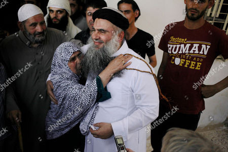 """Aisha, mother of radical al-Qaida-linked preacher Abu Qatada, hugs him as he arrives to his parents home in Amman, Jordan, . A Jordanian court on Wednesday acquitted Qatada - known for his fiery pro-al-Qaida speeches - of involvement in a plot to target Israeli and American tourists and Western diplomats in Jordan more than a decade ago. The three-judge panel unanimously acquitted Qatada """"because of the lack of convincing charges against him,"""" said Judge Ahmed Qattarneh. His father Mahmoud stands at left"""