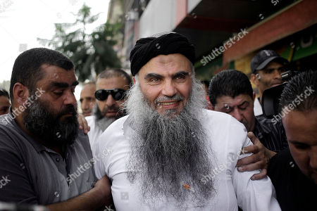 "Family and friends of radical al-Qaida-linked preacher Abu Qatada, center, greet him as he arrives to his family's home in Amman, Jordan, . A Jordanian court on Wednesday acquitted Qatada - known for his fiery pro-al-Qaida speeches - of involvement in a plot to target Israeli and American tourists and Western diplomats in Jordan more than a decade ago. The three-judge panel unanimously acquitted Qatada ""because of the lack of convincing charges against him,"" said Judge Ahmed Qattarneh"