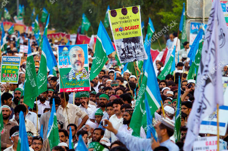 """Stock Image of Supporters of Pakistani religious party Jamaat-e-Islami hold a banner of Hamas leader Khaled Meshaal with wording """"We salute to Khaled's courage,"""" as they take part in a rally against the Israeli bombings in the Gaza Strip, in Islamabad, Pakistan"""