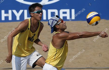 Wong Chun-wai, Chui Kam-lung Hong Kong's Wong Chun-wai, right, and Chui Kam-lung, left, return the ball to South Korea's Moon Jung-hyun and Lee Hee-yoon during their men's beach volleyball match at the 17th Asian Games at Songdo Global University Beach Volleyball Venue