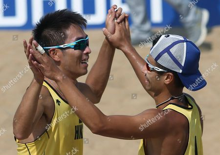 Wong Chun-wai, Chui Kam-lung Hong Kong's Wong Chun-wai, right, and Chui Kam-lung, left, celebrate after defeating South Korea's Moon Jung-hyun and Lee Hee-yoon during their men's beach volleyball match at the 17th Asian Games at Songdo Global University Beach Volleyball Venue