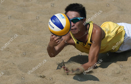 Chui Kam-lung Hong Kong's Chui Kam-lung dives to return the ball to South Korea's Moon Jung-hyun and Lee Hee-yoon during their men's beach volleyball match at the 17th Asian Games at Songdo Global University Beach Volleyball Venue