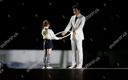 South Korean rhythmic gymnast Kim Min hands over a hoop to actor Jang Dong-gun during the opening ceremony for the 17th Asian Games in Incheon, South Korea