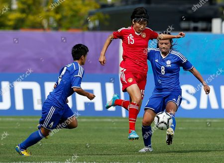 China's Zhang Rui kicks the ball past Taiwan's Lin Kai Ling, left, and her teammate Wang Hsiang Huei during their match at the 17th Asian Games in Incheon, South Korea
