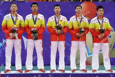 Stock Picture of Xu Xin, Zhang Jike, Ma Long, Zhou Yu, Fan Zhendong China's gold medalists Xu Xin, left, Zhang Jike, 2nd left, Ma Long, center, Zhou Yu, 2nd right, and Fan Zhendong, right, pose for photographers during a victory ceremony of the men's team table tennis competition at the 17th Asian Games in Incheon, South Korea