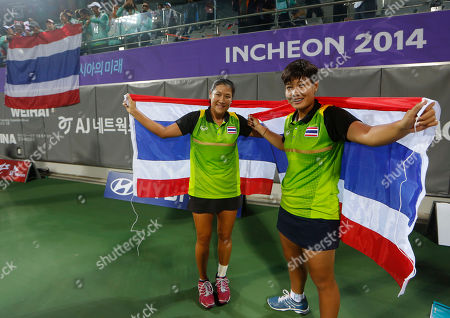 Stock Image of Luksika Kumkhum, Tamarine Tanasugarn Thailand's Luksika Kumkhum, right, and Tamarine Tanasugarn celebrate after winning the women's doubles gold medal tennis match at the 17th Asian Games in Incheon, South Korea