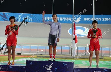 Zhong Tianshi, Lee Wai Sze, Lin Junhong Flanked by two China riders, Zhong Tianshi, left, silver, and Lin Junhong, right, bronze, Hong Kong Lee Wai Sze waves as she celebrates winning the women's sprint track cycling race at the 17th Asian Games in Incheon, South Korea