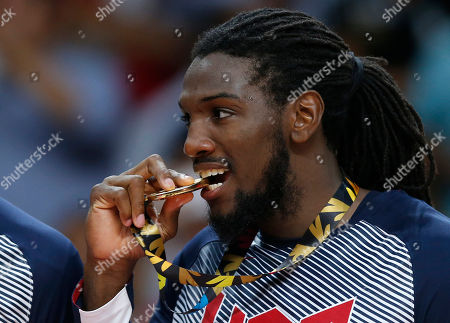 United States' Kenneth Faried bites his gold medal as he celebrates after wining the final World Basketball match against Serbia at the Palacio de los Deportes stadium in Madrid, Spain