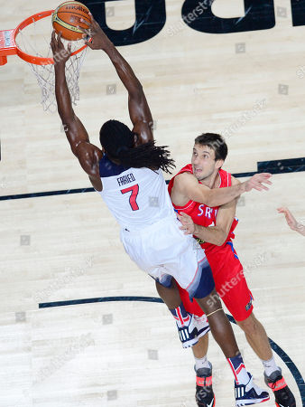 United States' Kenneth Faried, left, scores during the final World Basketball match between the United States and Serbia at the Palacio de los Deportes stadium in Madrid, Spain