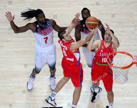 Serbia's Nemanja Bjelica, center, and Serbia's Nikola Kalinic, and United States' Kenneth Faried, left, vie for the ball during the final World Basketball match between the United States and Serbia at the Palacio de los Deportes stadium in Madrid, Spain