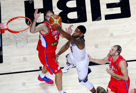 United States' Rudy Gay, center, scores against Serbia's Nenad Krstic, left, during the final World Basketball match between the United States and Serbia at the Palacio de los Deportes stadium in Madrid, Spain