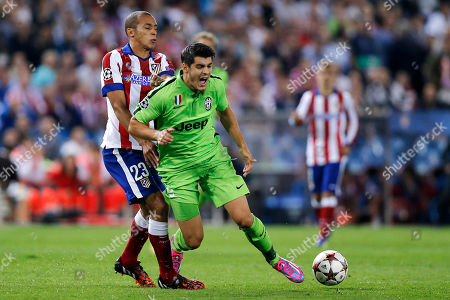 Juventus' Alvaro Morata, right, is tackled by Atletico's Joao Miranda, during the Group A Champions League soccer match between Atletico De Madrid and Juventus at the Vicente Calderon stadium in Madrid, Spain