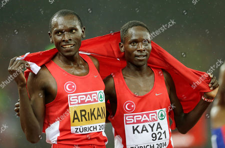 Turkey's Ali Kaya, right, who was third, and Turkey's Polat Kemboi Arikan, who finished fourth, pose with the flag after the 10 000m final during the European Athletics Championships in Zurich, Switzerland