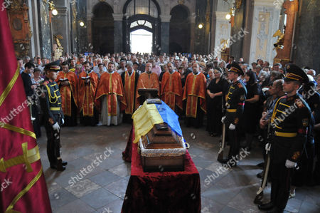 Priests pray for Ukrainian officer Andriy Rodin killed the war with pro-Russian separatists in Ukraine's east near Luhansk, as a coffin with his remnants covered with the national flag stays in St. Peter and Paul temple in Lviv, western Ukraine