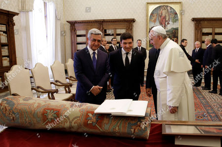 Pope Francis listens to an unidentified translator next to Armenia's President Serge Sarkisian, left, in front of a tapestry and a framed document, two gifts from Armenia's president for the pontiff, during their private audience in the pope's private studio, at the Vatican