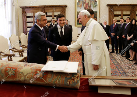 Pope Francis and Armenia's President Serge Sarkisian, left, shakes hands during their private audience in the pontiff's private studio, at the Vatican, . In between the pontiff and the Armenian president is an unidentified translator