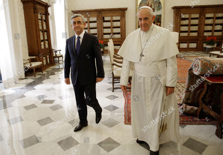 Pope Francis walks with Armenia's President Serge Sarkisian, left, during a private audience in the pontiff's private studio, at the Vatican