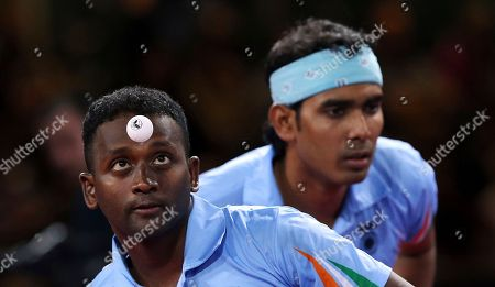 10ThingstoSeeSports - India's Arputharaj Anthony, foreground serves, as Sharath Kamal Achanta stands near during their match against Singapore's Jian Zhan and Zi Yang, in the Men's Doubles Table tennis Semi-final, at Hampden Park Stadium, during the Commonwealth Games 2014 in Glasgow, Scotland