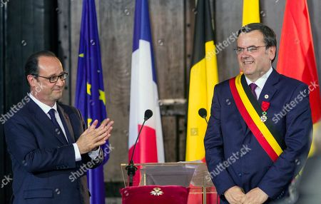 French President Francois Holland, left, applauds as he presents the Legion of Honour medal to the Liege Mayor Willy Demeyer, during a commemoration ceremony to mark the 100th anniversary of the outbreak of World War I at the Town Hall in Liege, Belgium, on . The national ceremony pays homage to the numerous victims of the war, both soldiers and civilians, from both Belgium and abroad who lost their lives on Belgian soil