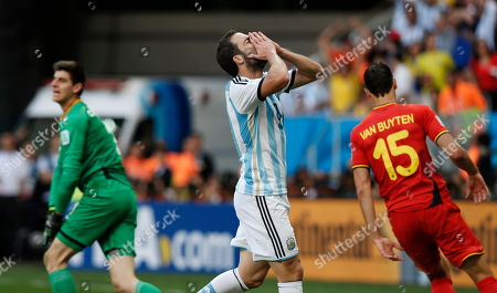 Argentina's Gonzalo Higuain reacts after missing a chance to score during the World Cup quarterfinal soccer match between Argentina and Belgium at the Estadio Nacional in Brasilia, Brazil, . Left is Belgium's goalkeeper Thibaut Courtois and right Belgium's Daniel Van Buyten