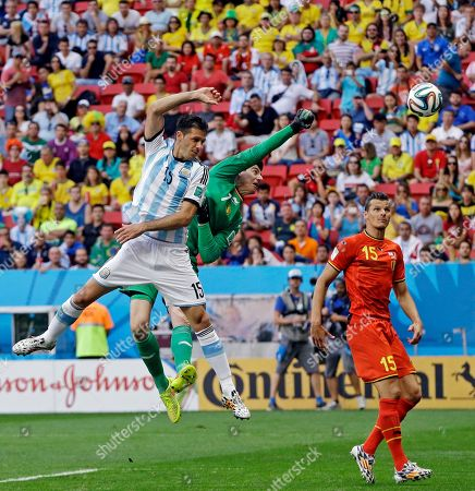 Belgium's Daniel Van Buyten (15) watches as goalkeeper Thibaut Courtois clears the ball away from Argentina's Martin Demichelis during the World Cup quarterfinal soccer match at the Estadio Nacional in Brasilia, Brazil