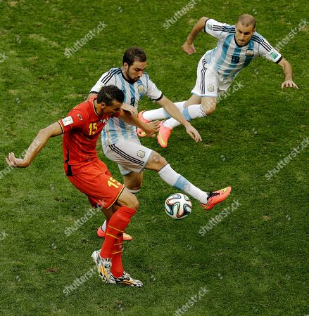 Belgium's Daniel Van Buyten, left, controls the ball next to Argentina's Gonzalo Higuain, center, and Rodrigo Palacio, right, during the World Cup quarterfinal soccer match between Argentina and Belgium at the Estadio Nacional in Brasilia, Brazil