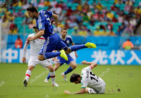 Bosnia's Sead Kolasinac leaps over the challenge of Iran's Pejman Montazeri during a group F World Cup soccer match between Bosnia and Iran at the Arena Fonte Nova in Salvador, Brazil