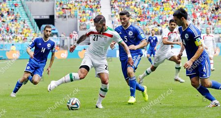 Iran's Ashkan Dejagah shoots a pass to Iran's Pejman Montazeri, rear, through Bosnia's Sead Kolasinac (5) and Emir Spahic (4), during the group F World Cup soccer match between Bosnia and Iran at the Arena Fonte Nova in Salvador, Brazil, . At left is Bosnia's Tino-Sven Susic (14