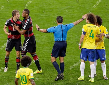 Referee Marco Rodriguez from Mexico mediates between Germany's Thomas Mueller, left, and Brazil's David Luiz (4) during the World Cup semifinal soccer match between Brazil and Germany at the Mineirao Stadium in Belo Horizonte, Brazil