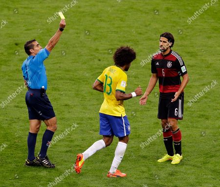 Referee Marco Rodriguez from Mexico shows a yellow card to Brazil's Dante during the World Cup semifinal soccer match between Brazil and Germany at the Mineirao Stadium in Belo Horizonte, Brazil, . At right Germany's Sami Khedira