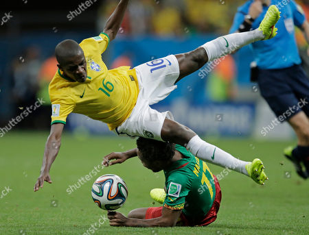 Brazil's Ramires falls over Cameroon's Jean Makoun during the group A World Cup soccer match between Cameroon and Brazil at the Estadio Nacional in Brasilia, Brazil
