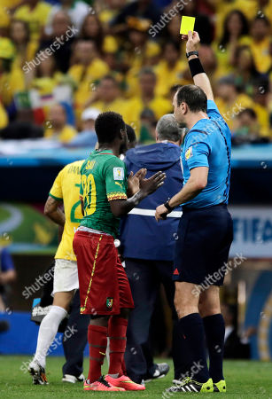 Stock Picture of Referee Jonas Eriksson from Sweden books Cameroon's Edgar Salli after Salli kicked Brazil's Dani Alves during the group A World Cup soccer match between Cameroon and Brazil at the Estadio Nacional in Brasilia, Brazil