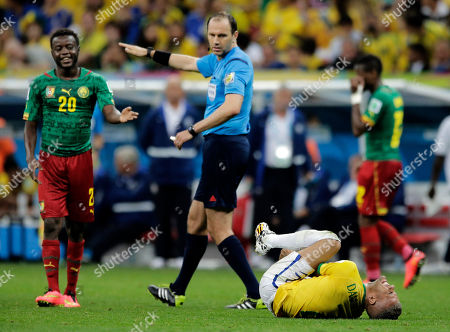 Referee Jonas Eriksson from Sweden signals to Cameroon's Edgar Salli after Salli kicked Brazil's Dani Alves during the group A World Cup soccer match between Cameroon and Brazil at the Estadio Nacional in Brasilia, Brazil