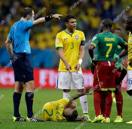 Referee Jonas Eriksson from Sweden signals as Brazil's Thiago Silva (3) argues with Cameroon's Landry N'Guemo after Brazil's Dani Alves (2) was kicked by Cameroon's Edgar Salli during the group A World Cup soccer match between Cameroon and Brazil at the Estadio Nacional in Brasilia, Brazil