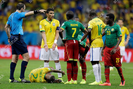 Referee Jonas Eriksson from Sweden signals as Brazil's Thiago Silva (3) argues with Cameroon's Landry N'Guemo after Brazil's Dani Alves (2) was kicked by Cameroon's Edgar Salli (20) during the group A World Cup soccer match between Cameroon and Brazil at the Estadio Nacional in Brasilia, Brazil
