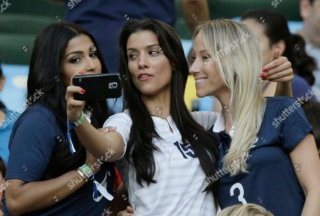 Sandra Evra, right, wife of France's Patrice Evra, and Ludivine Sagna, center, wife of France's Bacary Sagna, take a selfie prior to the group E World Cup soccer match between Ecuador and France at the Maracana Stadium in Rio de Janeiro, Brazil