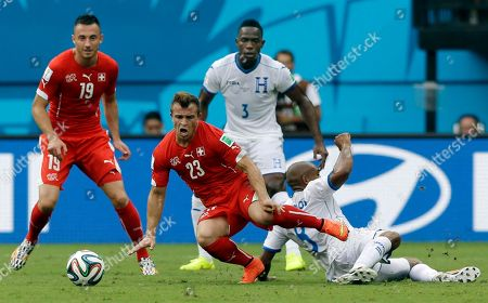 Stock Image of Switzerland's Xherdan Shaqiri (23) is fouled by Honduras' Wilson Palacios during the group E World Cup soccer match between Honduras and Switzerland at the Arena da Amazonia in Manaus, Brazil, . Switzerland's Josip Drmic (19) and Honduras' Maynor Figueroa (3) watch from behind