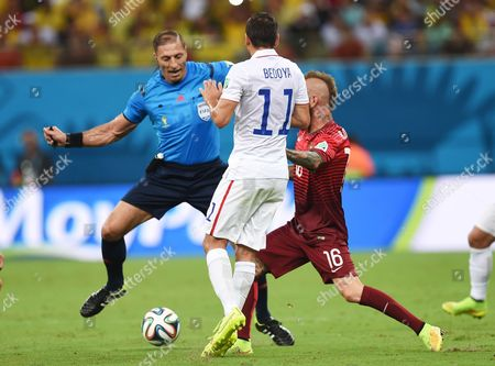 Referee Nestor Pitana from Argentina, left, gets caught up in play as United States' Alejandro Bedoya and Portugal's Raul Meireles, right, battle for the ball during the group G World Cup soccer match between the USA and Portugal at the Arena da Amazonia in Manaus, Brazil